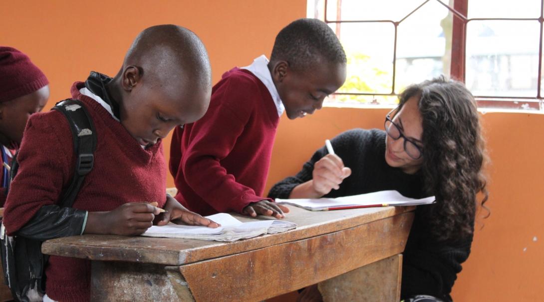 Joven voluntaria de 15 años ayudando a niños pequeños con inglés básico.